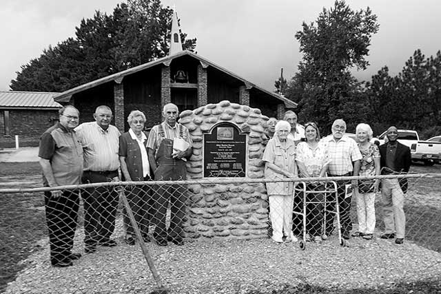 Aline Baptist Church celebrated its 100th anniversary on Sunday, Aug. 21, precisely 100 years from its beginning on Aug. 21, 1916, with the dedication of a stone-encased Texas Historical Marker.  Pictured (L-R) are Buddy McDaniel, DeWayne Ling, Deloris Griffith, Durwood Ling, Michael Penecost, Evelyn Mahan, Bobby Penecost, Sharon Penecost, Wayne Penecost, Judy Mahan Brown and Texas Rep. James White.  The marker project was mostly led by brothers Durwood and De Wayne Ling who live just a few stone-throws away.
