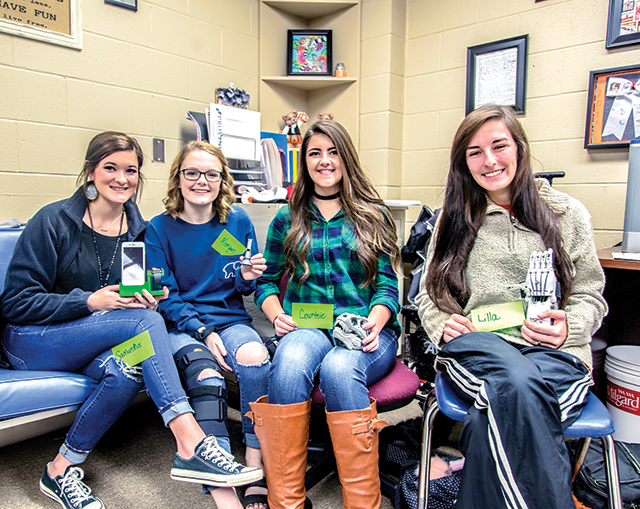 Warren ISD Tech Team display 3D printed items—Shown, from left, are  Samantha Rothenberger, Morgan Clancy, Courtnie Wheeler, Lilla Jackson. (Not pictured: Colton Haynes, Brice Moore, Cole Stanley, Jeremy Chessher.) (Hale Hughes Photo)